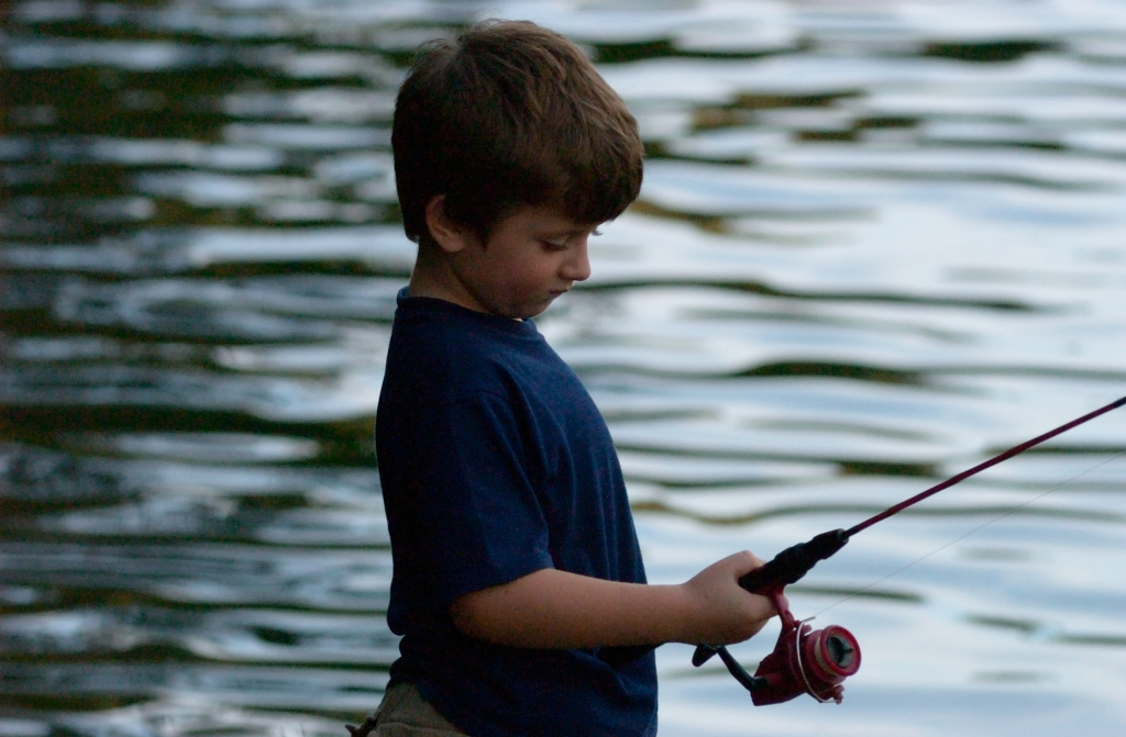 Child with fishing rod engaged completely in waiting for that first strike
